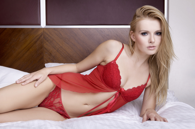 Beautiful young blonde woman in red lingerie on the bed